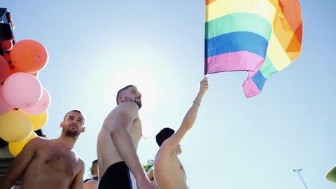 STRASBOURG, FRANCE - JUN 10, 2017: Beautiful males dancing on the truck during gay pride parade waving Gay pride flag