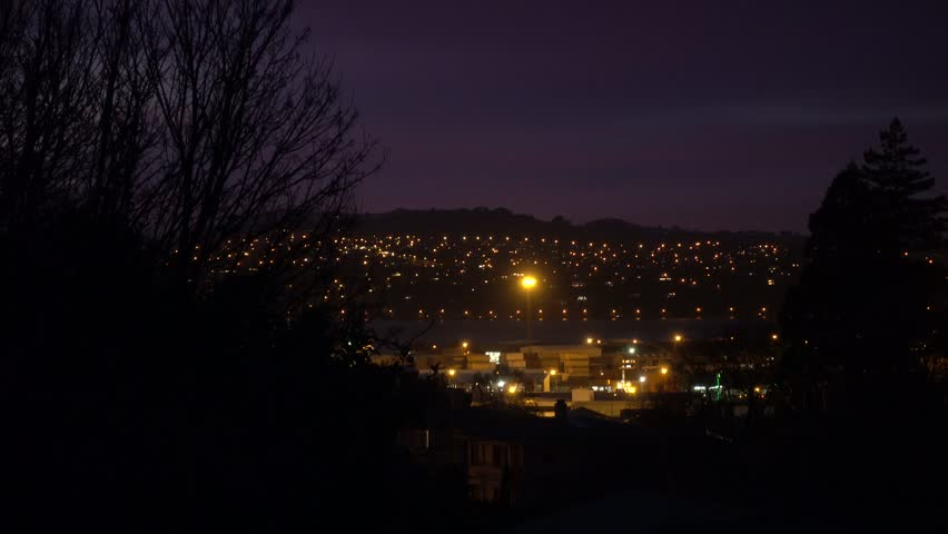 Early morning footage of city against mountain hill on a partial red lit night sky. Peninsula in the background