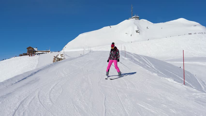 Shot in movement, front view, a beginner alpine skier woman carefully and slowly skiing down on the slope plow putting the ski brake, on snowy mountain slopes background. Slow motion, 4k, 3840x2160 | Shutterstock HD Video #1013182589