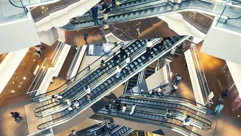 People on many fast moving Escalators In big modern shopping mall. Consumption concept. Time lapse