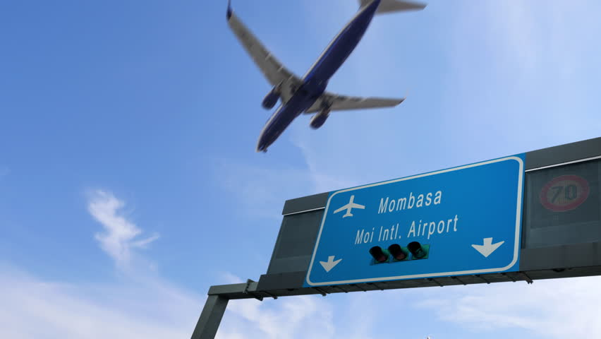 airplane flying over mombasa airport signboard