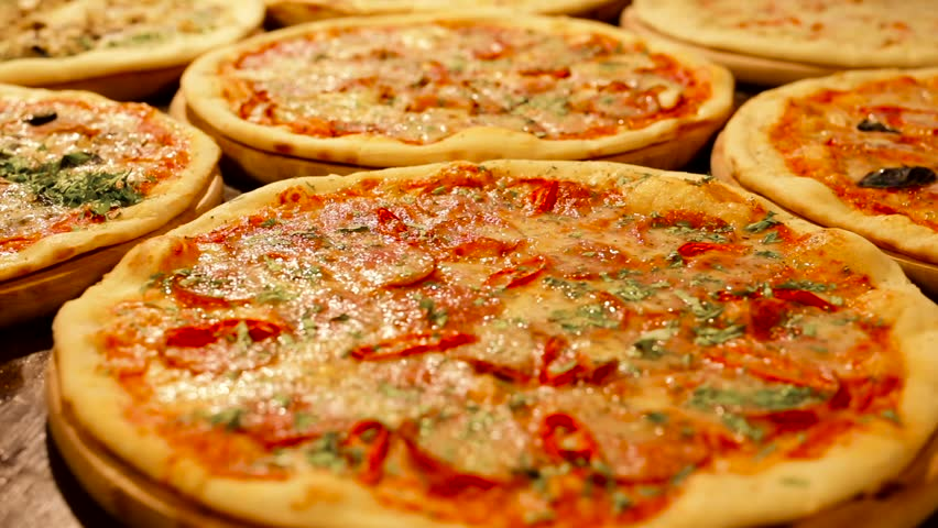 Many kinds of Italian Hot and Tasty Pizza on the Wooden Table. Big Sizes Pizzas at the Kitchen. Italian Dishes. Pizza with Herbs, Pepper, Sausage, Melted Cheese. Well Baked Dish.