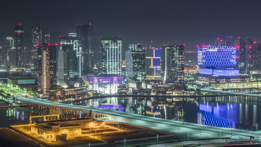 Aerial skyline of Abu Dhabi city centre from above during all night timelapse with illuminated skyscrapers and blinking light in windows. Light swithcing off. Traffic on the road.