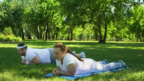 Fat people doing plank exercise, overcoming laziness and exhaustion, strong will