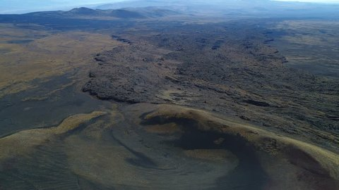 Aerial drone scene of La Payunia National Park in Malargüe, Mendoza. Pampas Negras with black, red ground rocks from volcano and golden grasses pattern. Herradura volcano. Bed of lava.