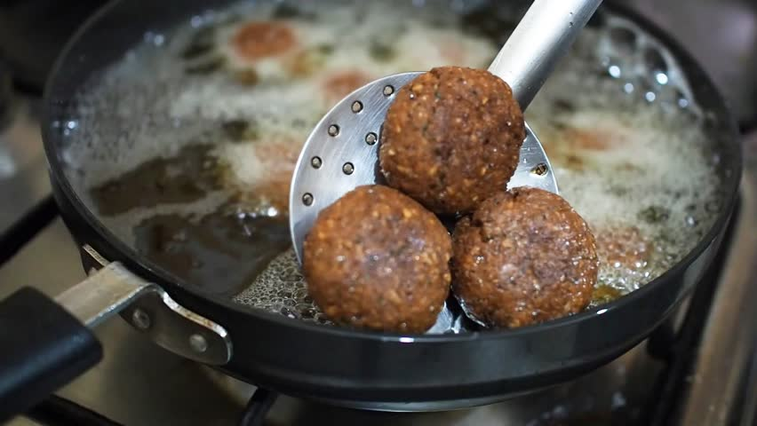 A close of a street vendor deep frying falafels in hot bubbling oil in a pan