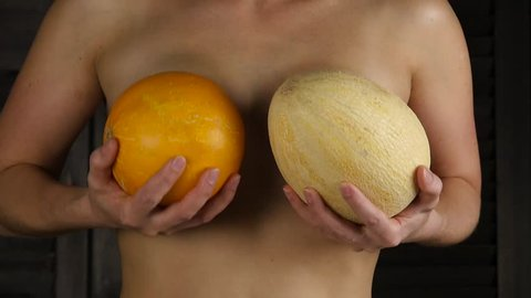 Young happy woman holds two melons above her breast. Plastic surgery and silicone implants concept. slow motion