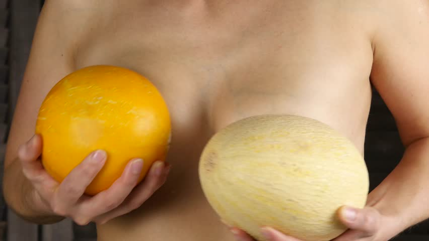 Young happy woman holds two melons above her breast. Plastic surgery and silicone implants concept. 4K