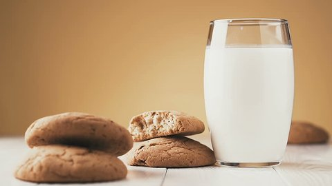 Hand dipping a cookie into glass of milk, slow motion.