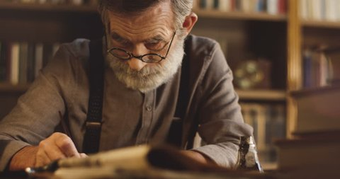 Portrait of the senior Caucasian professor in glasses writing something while sitting in his cabinet or library room. Close up.