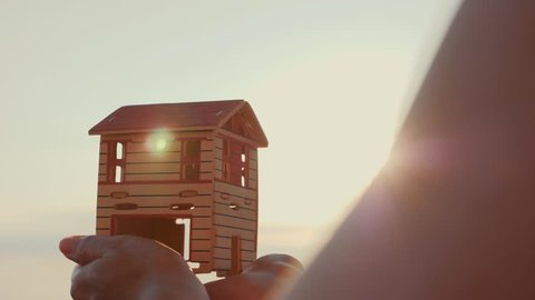 Silhouette of a paper house in hands at sunset in the sun.
