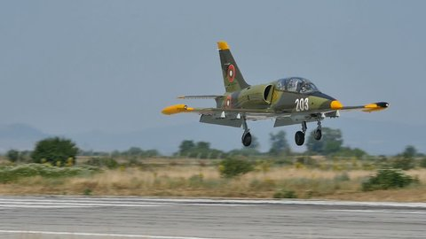 Green Camouflage Military Light Combat Jet Aircraft Aero Vodochody L-39 Albatros Landing in Slow Motion. L-39 is a Soviet Era Jet used by Warsaw Pact Air Forces. Graf Ignatievo Bulgaria 26 June 2016