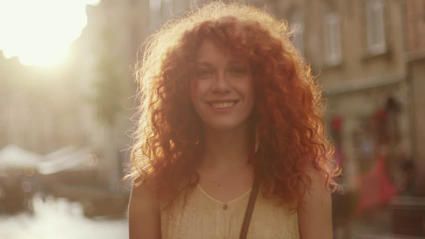 Sunshine young smiling woman with red curly hair look at camera smile walking in the city streets portrait happy slow motion summer face sunset beautiful lady outdoor closeup cute | Shutterstock HD Video #1013313149