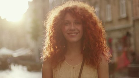 Sunshine young smiling woman with red curly hair look at camera smile walking in the city streets portrait happy slow motion summer face sunset beautiful lady outdoor closeup cute