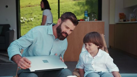 Handsome bearded businessman works via laptop at home, his lovely little son sits down near dad, father gives a kid fruit to taste, his cute wife takes care of their daughter on the background.