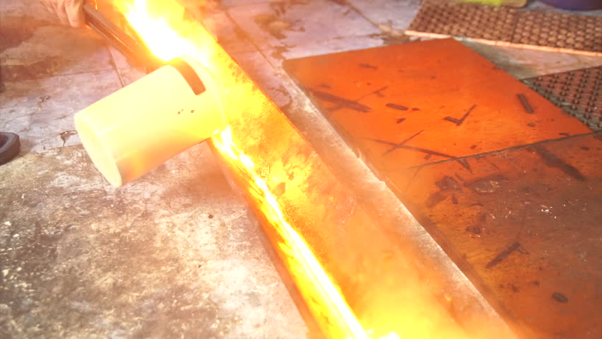 Molten silver being poured from a crucible into an ingot mold with the light coming from the molten silver. in the industrial workshop. detail hot silver