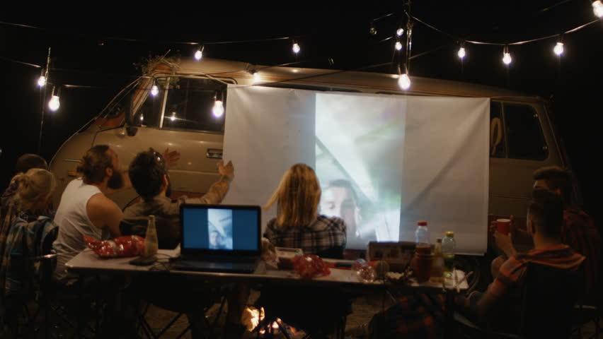 Group of people relaxing around bonfire in campsite watching memorable videos on screen on van in night having fun #1013353469