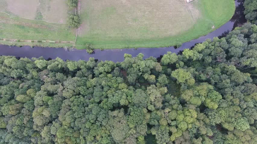 Drone shot flying over the river la Sarthe in the village Saint-Ceneri-le-Gerei discovering a Chapel. Medium altitude flight, cloudy day. Location France