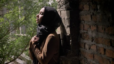 Young muslim woman in black hijab holding her hands and looking upwards, standing in abandoned brick building