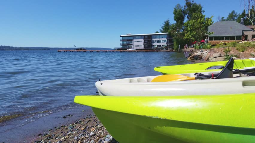 Three kayaks in closeup laying by the seashore during summer, people sunbathing in background