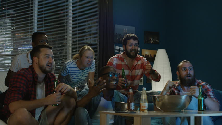 Group of multiracial men and woman on sofa watching sport game they are unhappy with the result of the game | Shutterstock HD Video #1013428289