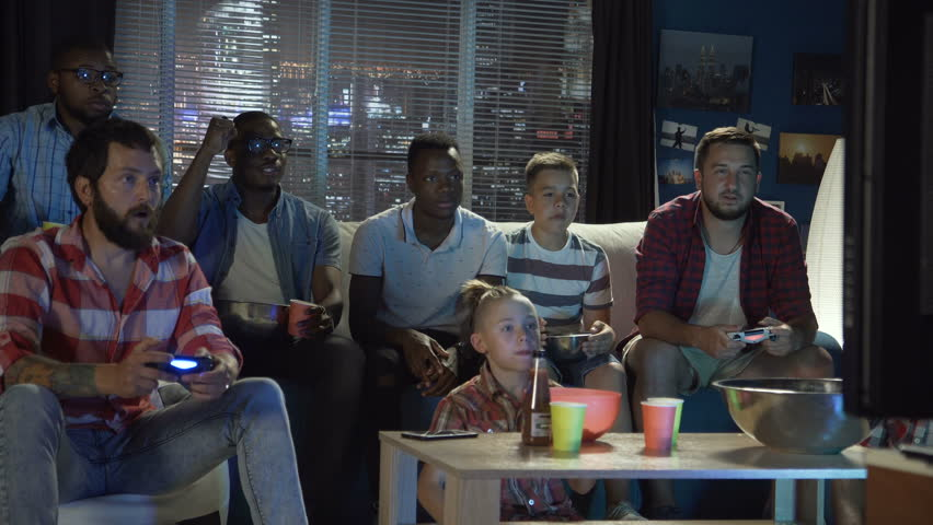 Group of multiethnic men and teens gathering on sofa at home and playing videogame with gamepads | Shutterstock HD Video #1013428349