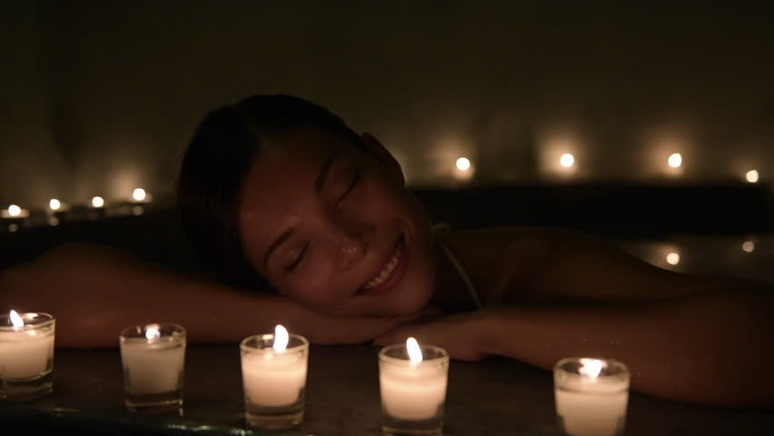 Beautiful woman relaxing in hot bath tub. Steam is coming out from water in Jacuzzi. Beauty spa is decorated with lit candles.