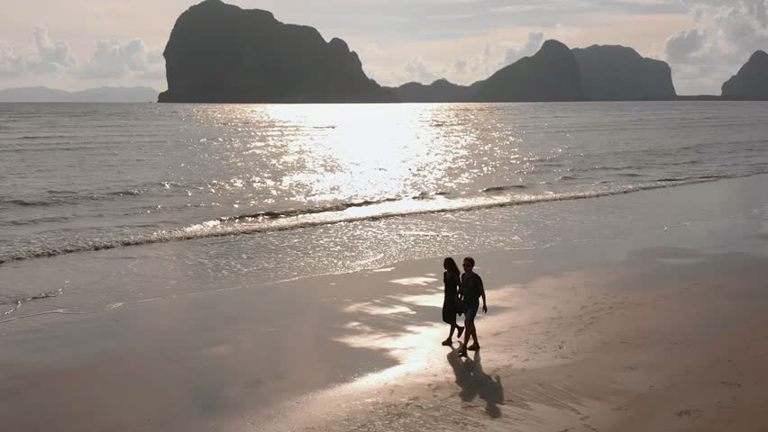 Young romantic couple walking on beach. Sun Flares. Romantic happy young couple enjoying ocean sunset during travel