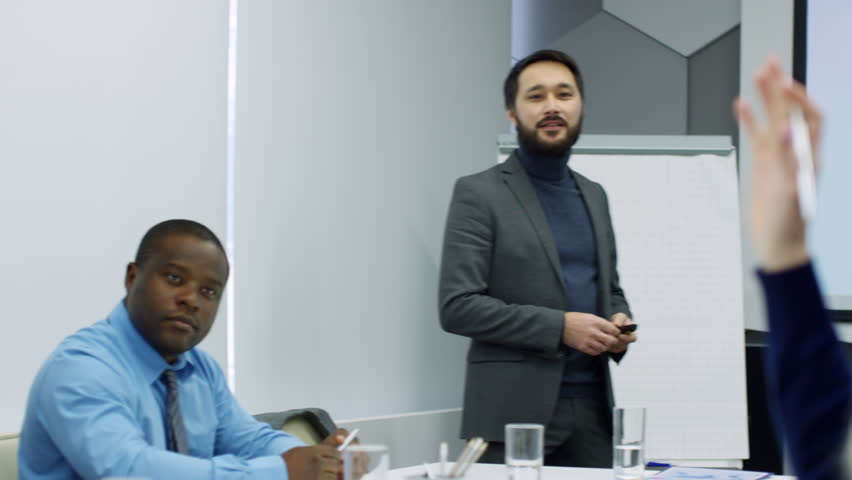 Asian businessman standing at whiteboard and using remote while giving presentation to multi-ethnic team of colleagues during meeting | Shutterstock HD Video #1013440739