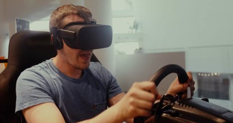 Computer simulation. Cheerful young gamer in virtual reality goggles is expressing excitement while enjoying car racing video game with steering wheel