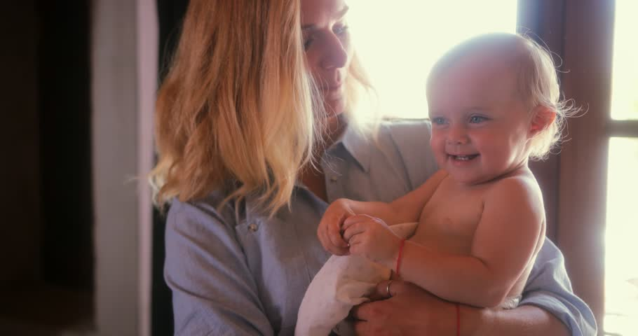 Young mother at home holding little laughing baby with blue eyes and blond hair | Shutterstock HD Video #1013444669