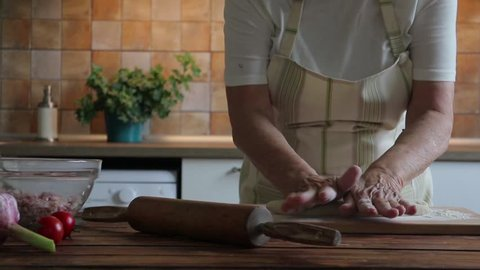 Old woman is making dough for dumplings, slow motion video