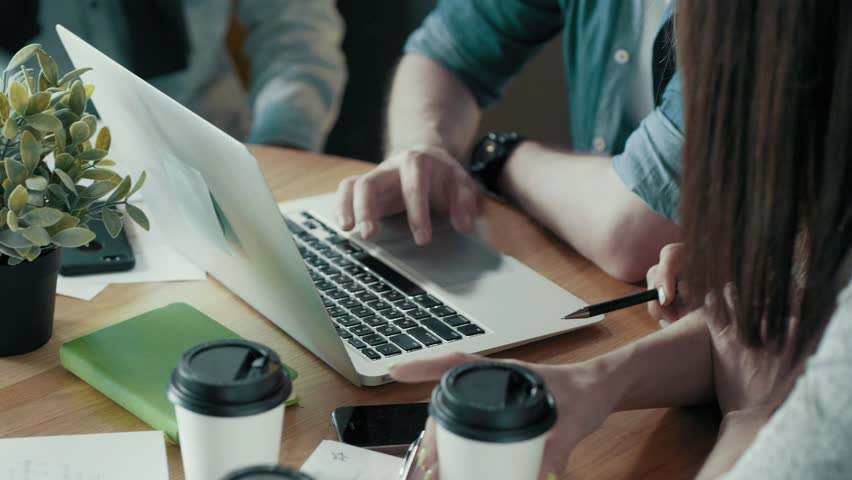 Dolly shot modern start up office desk with devices papers documents coffee creative business team meeting and brainstorming using digital display technology discussing project male hands use laptop   Shutterstock HD Video #1013484989