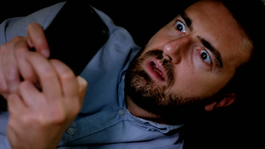 The video is about one surprised man reading unexpected news on the mobile phone at night.The shot is fixed on the man