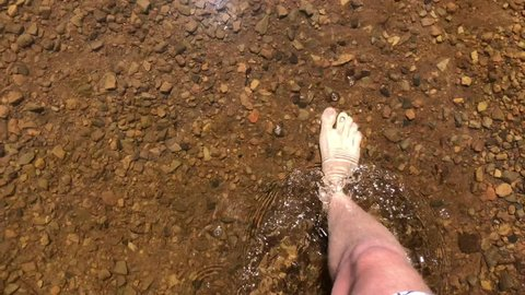 A person's legs walking through glimmering water. The water is very clear, and you can see the brown pebbles underneath. All very pretty.