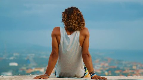 SLOWMO, a young man sits overlooking a coastal city as the wind blows his hair and tank top. Willemstad, Curacao
