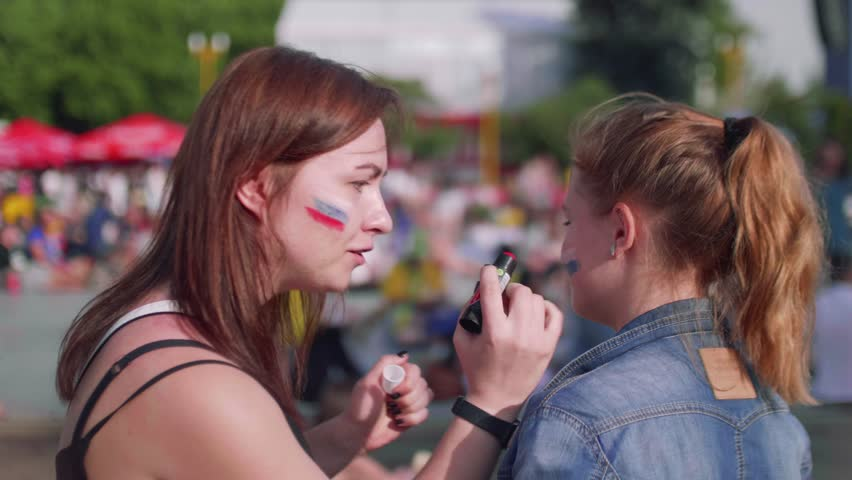 Girls get ready to cheer for Russian team in fan zone during football match   Shutterstock HD Video #1013519879