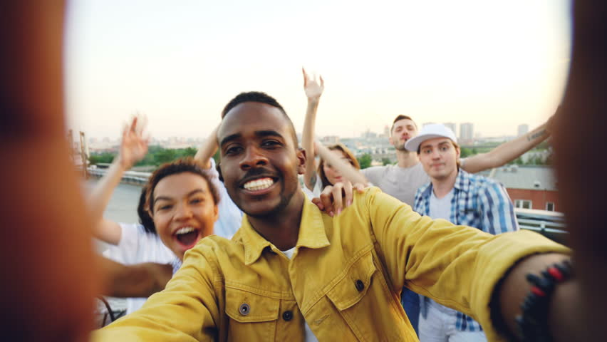 Point of view shot of handsome African American man partying with friends on rooftop, dancing and having fun with drinks. Sky and beautiful city is visible.