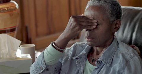 Elderly senior black woman rubbing her forehead to relieve headache pain from a sinus cold, allergies, or flu symptoms