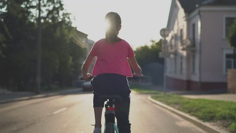 Child Girl Riding Bike at Sunset. 4K Back View