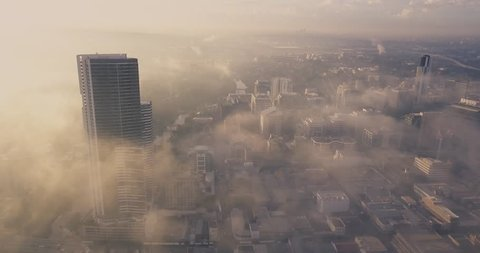 Morning sunrise with fog and mist low to the ground. Buildings casting a shadow on the mist. City scape, bustling metropolis view from an aerial perspective.