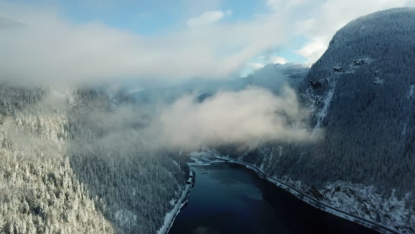 Aerial footage of flying through a cloud in the mountains over a lake during the winter while it was snowing lightly