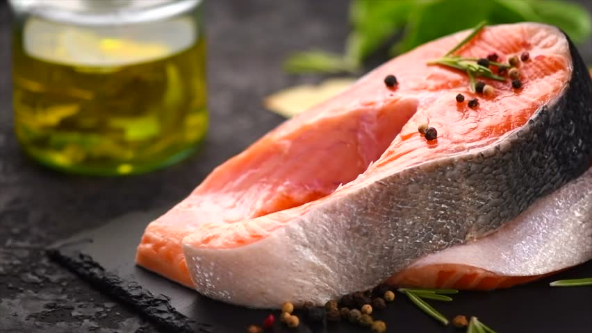Raw Trout Red Fish Steak with Herbs and Lemon and olive oil, spices and herbs on black stone slate. Cooking Salmon, sea food. Healthy eating concept. Salmon. Dolly shot. Slow motion 4K UHD video