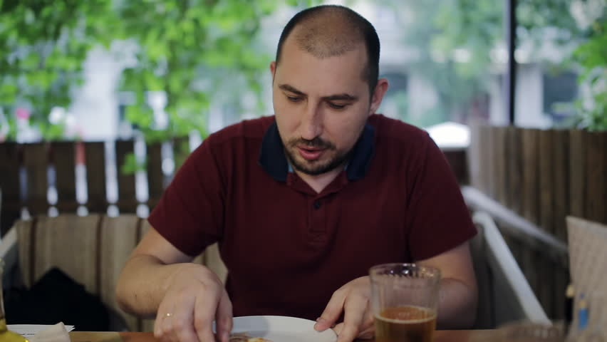 A young man sitting with a friend in a pizzeria drinking beer clinking glasses. Communication after a working day | Shutterstock HD Video #1013613809
