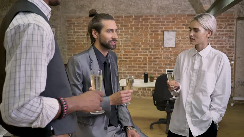 Three multy-ethnic workers tell stories, sitting in office, drinking champagne, communication concept | Shutterstock HD Video #1013617079