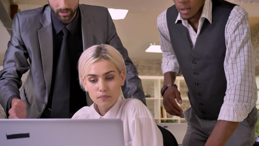 Pretty businesswoman asks her colleagues their attitude to her ideas on laptop, business concept, communication concept | Shutterstock HD Video #1013617109