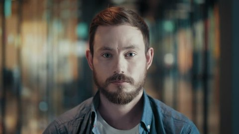 Portrait of creative young male with beard and mustache face of european serious guy in modern big start up office casual man looks pensive severe look blinks and frowns