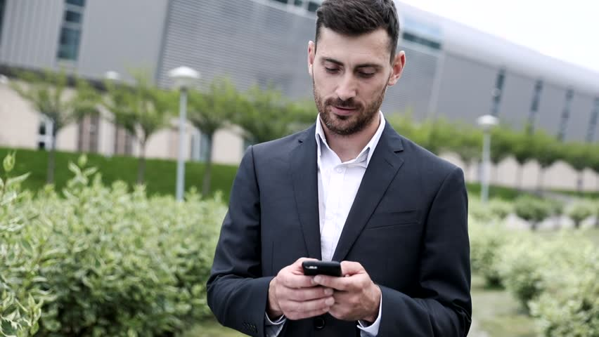 Attractive Young Office Worker Standing in the City Park. Using Social Networks on his Phone.  | Shutterstock HD Video #1013630789