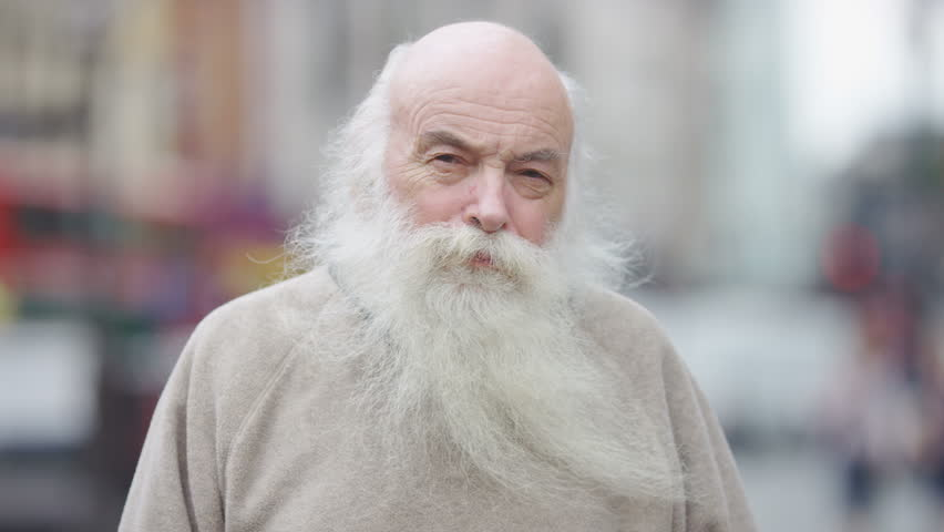 Portrait of a senior man with a big beard looking to camera with a straight expression | Shutterstock HD Video #1013652419