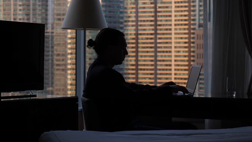 Black silhouette of laptop user against window, man sitting at table, push buttons to finish work, stand up and walk away. Blurred mansion building seen outdoors. Man wear suit and have back knot hair   Shutterstock HD Video #1013663459
